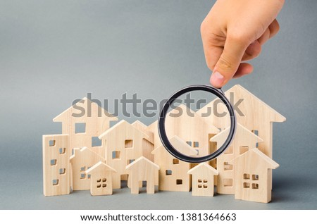 Wooden houses and magnifying glass. Property valuation. Home appraisal. Choice of location for the construction. House searching concept. Search for housing and apartments. Real estate #1381364663