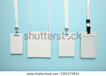 Set of tag id pass, plastic identification on blue background. White blank badge mockup. #1381374854