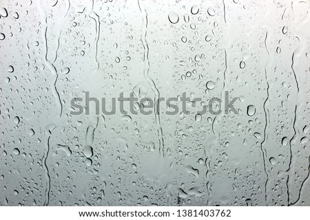 A small raindrop rests on the glass after rain. #1381403762