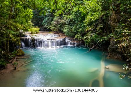 Waterfall and blue emerald water color in Erawan national park. Erawan Waterfall tier, Beautiful nature rock waterfall steps in tropical rainforest at Kanchanaburi province, Thailand #1381444805