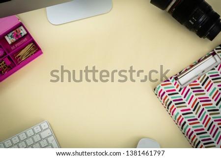 yellow desk with a camera, a floral notebook an a computer an a camera lenses. #1381461797