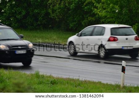 Hanau/Germany - 04.26.2019: Fast moving car (blurred) in germany on a rainy day #1381462094
