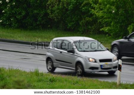 Hanau/Germany - 04.26.2019: Fast moving car (blurred) in germany on a rainy day #1381462100