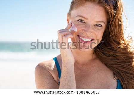 Smiling young woman applying sunscreen lotion on face at beach, with copy space. Portrait of beautiful happy girl using sunblock on her delicate skin with freckles and looking at camera. #1381465037