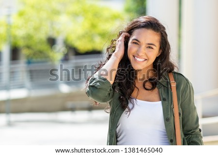 Happy young beautiful woman walking on the street. Portrait of cheerful university student looking at camera while adjusting curly hair with copy space. Latin stylish girl smiling while standing. #1381465040