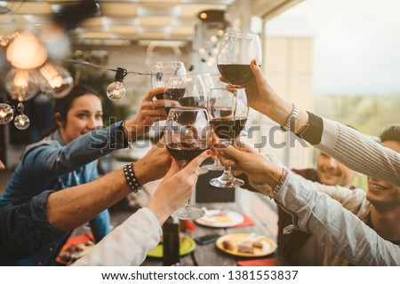 Young friends celebrating at dinner at sunset - Detail of hands while toasting with glasses of wine - Happy people at a terrace party after the harvest before sunset - Concept of friendship Royalty-Free Stock Photo #1381553837