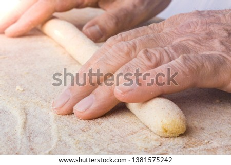 Hands of a man is making homemade potato dumplings on wooden cutting board with whole wheat flour #1381575242