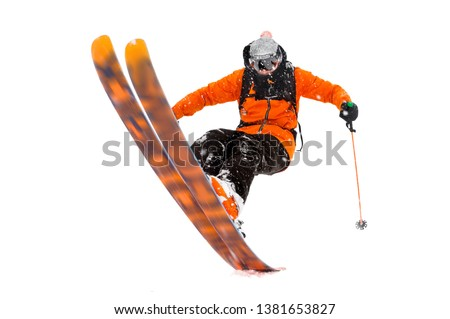 The athlete skier in the orange black suit does the trick on the back of the skis. real photo made in the mountains isolated on white background