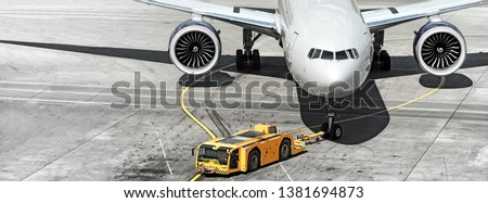 airplane on airport runway with pushback tractor attached to plane nose gear aerial top front view passenger jet engine aircraft towing by ground vehicle to terminal gate black and white wide banner Royalty-Free Stock Photo #1381694873