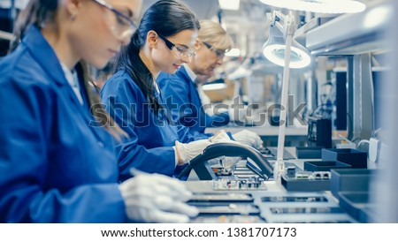 Female Electronics Factory Workers in Blue Work Coat and Protective Glasses Assembling Printed Circuit Boards for Smartphones with Tweezers. High Tech Factory with Employees. #1381707173