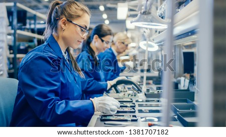 Female Electronics Factory Workers in Blue Work Coat and Protective Glasses Assembling Printed Circuit Boards for Smartphones with Tweezers. High Tech Factory with more Employees in the Background. #1381707182