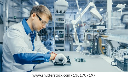 Young Man in Blue and White Work Coat is Using Plier to Assemble Printed Circuit Board for Smartphone. Electronics Factory Workers in a High Tech Factory Facility. #1381707197