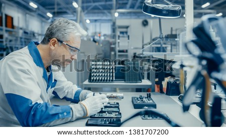 Senior Man in Blue - White Work Coat is Using Plier to Assemble Printed Circuit Board for Smartphone. Electronics Factory Workers in a High Tech Factory Facility. #1381707200