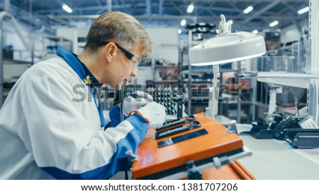 Man in Blue Work Coats is Using Tweezers to Assemble Printed Circuit Boards for Smartphones. Electronics Factory Workers in a High Tech Factory Facility. #1381707206