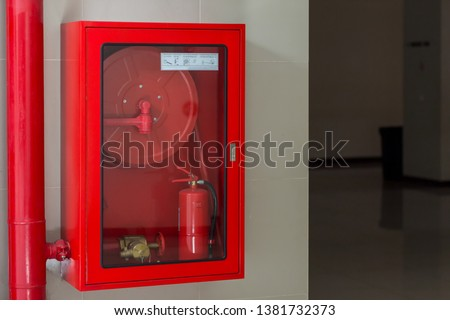 Hydrant with water hoses and fire extinguish equipment. Fire safety equipment in the red box on wall cement . Hydrant with water hoses and fire extinguish equipment / fire hose box . #1381732373