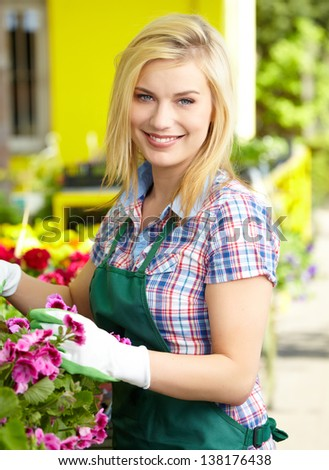 Florists woman working with flowers at a greenhouse. #138176438