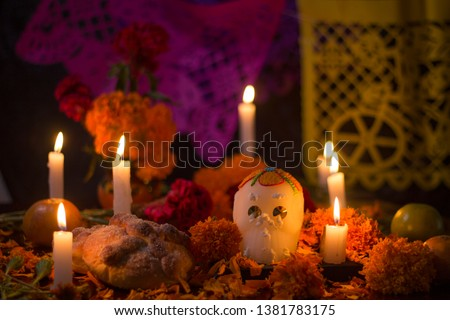 Sugar skull with candles, bread and flowers decoration for the day of the dead altar mexican tradition Royalty-Free Stock Photo #1381783175