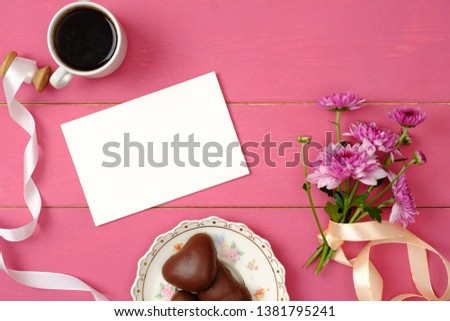 Woman table top view. Blank greeting card, envelope, coffee cup, ribbon, flowers, heart-shaped chocolate on pastel pink background. Female desk with feminine accessories. Top view, flat lay #1381795241