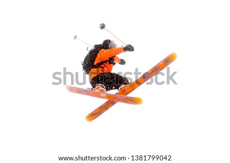 The athlete skier in the orange black suit does the jump trick by crossing the skis. real photo made in the mountains isolated on white background