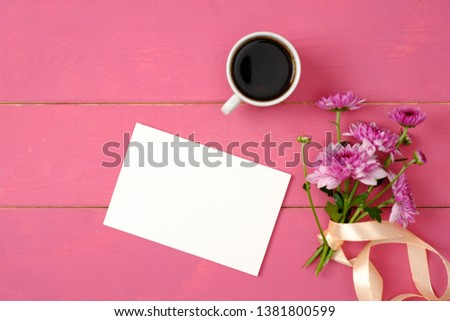 Blank greeting card, flowers and coffee cup on pink background. Top view, flat lay style composition. Feminine accessories on the wooden table.  #1381800599