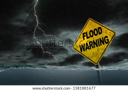 Flood Warning sign submerged in rising water against a stormy background with rain and lightning. Dirty and angled sign adds to the drama. #1381881677