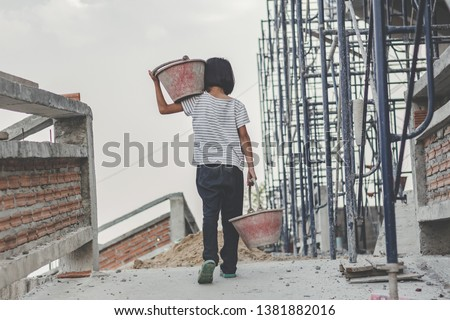 Children working at construction site for world day against child labor concept: Royalty-Free Stock Photo #1381882016