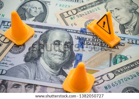 Traffic cone and dangerous under construction warning sign area on US dollar banknotes bill background. Concept of fix, repair, USA or global world economy financial crisis solution, loan refinance.