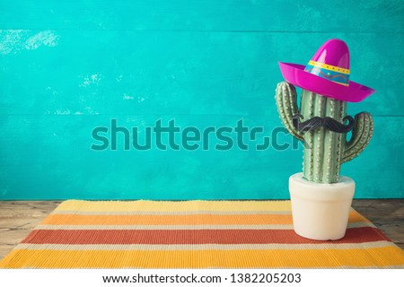 Cinco de Mayo holiday background with Mexican cactus and  party sombrero hat on wooden table  #1382205203