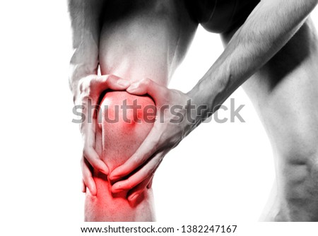young sport man with strong athletic legs holding knee with his hands in pain after suffering ligament injury during a running workout training isolated on white background #1382247167