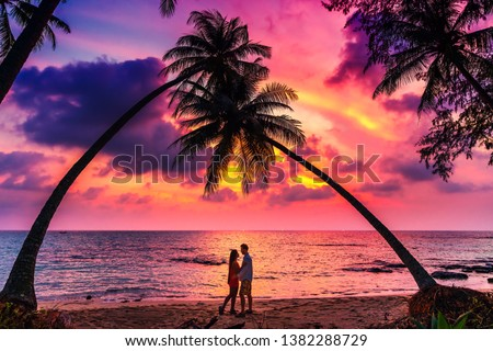 Silhouette of romantic affectionate couple kissing at sunset sea beach. Dating and relationship background with copyspace. Man and woman in love in honeymoon vacation. #1382288729
