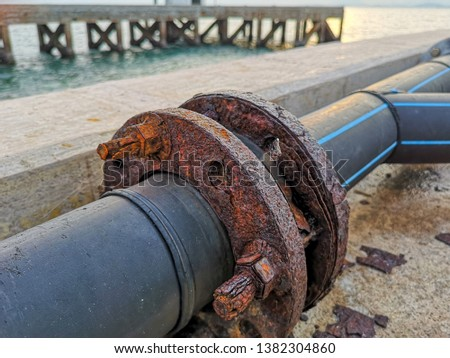 Marine corrosion in the form of general attack on carbon steel flanges or metal equipment on pier. Area most affected is wet and dry zones. Severe corrosion was evidenced by corrosion product layers. #1382304860