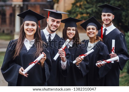 Happy graduates. Five college graduates standing in a row and smiling. Nice time! #1382310047