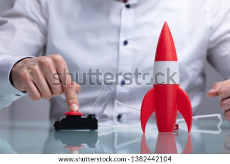 Businessman's Hand Launching Rocket By Pressing Red Button #1382442104