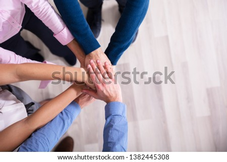 An Elevated View Of Businesspeople Stacking Hands Over Each Other #1382445308