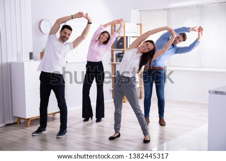 Group Of Happy Young Businesspeople Doing Stretching Exercise In Office #1382445317