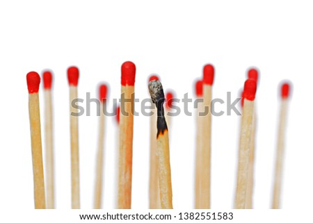 A burned match stands against a white background, next to it and behind are intact matches with a red head. Concept for burnout and exhaustion #1382551583