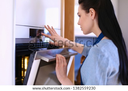 Beautiful young woman checking how her cake is doing in the oven #1382559230