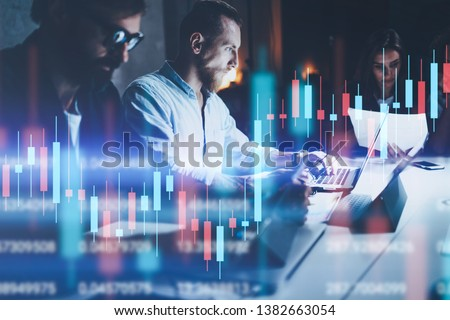 Business team working together at night office.Technical price graph and indicator, red and green candlestick chart and stock trading computer screen background. Double exposure. #1382663054