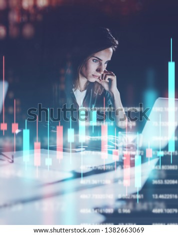 Young woman working at night modern office loft.Red and green candlestick chart and stock trading on background. Double exposure #1382663069