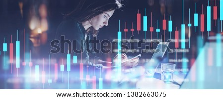 Business woman sitting at night office in front laptop computer and using her mobile phone. Red and green candlestick chart and stock trading computer screen background. Double exposure. Wide #1382663075