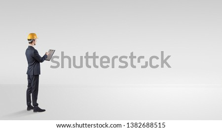 Young architect with construction helmet standing in an empty space and holding a plan #1382688515