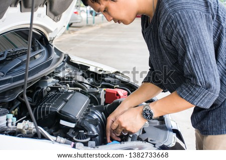 Man or auto mechanic worker checking the car engine oil and maintenance before traveling for safety. #1382733668