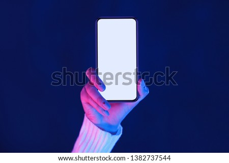 Woman's hand showing smartphone screen in neon blue and pink lights Royalty-Free Stock Photo #1382737544