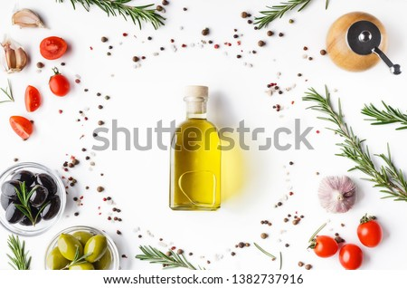 Fresh olives and oil in bottle with rosemary on white background with scattered cherry tomatoes end spicies, top view. Food background concept #1382737916