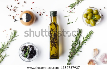 Fresh olives and oil in bottle with rosemary on white background with scattered spicies, top view #1382737937