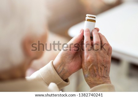 Senior woman about to take her medication #1382740241