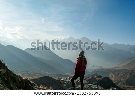 A girl wearing pink jacket standing on a top of a mountain and enjoying the misty Himalaya range spreading in front of her. The sun light is nicely marked. Freedom and achievement. #1382753393