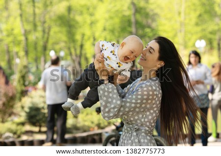 Mother and child laughing and playing in the summer on the nature background #1382775773