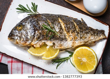 Baked dorado fish on white plate with lemon and rosemary. Top view, copy space. #1382777393
