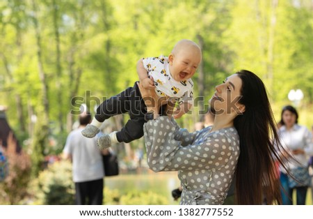 A Cute kid boy with his mother on a summer meadow #1382777552